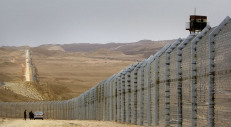 Egyptian border guards (R) observe from a watch tower as their Israeli counterparts supervise the construction of a border fence along Israel's border with Egypt near the Red Sea resort town of Eilat on February 15, 2012. Far from the uproar of Cairo's Tahrir Square, Israel has been doubling its efforts to erect a giant, impenetrable security barrier along its 240-kilometre (150-mile) border with the Egyptian Sinai. AFP PHOTO/AHMAD GHARABLI        (Photo credit should read AHMAD GHARABLI/AFP/GettyImages)